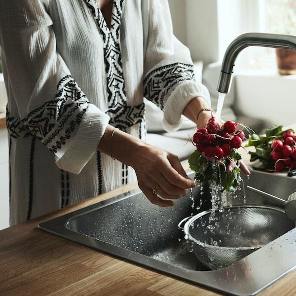 Kobieta myjąca pęczek rzodkiewem w zlewie kuchennym.