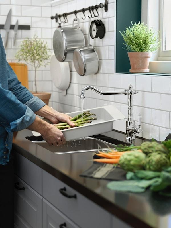 Kobieta myjąca szparagi w zlewie kuchennym z baterią GLITTRAN.