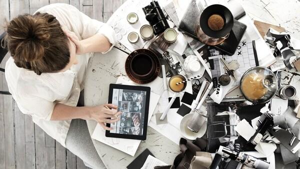 Kobieta ogldająca inspiracje na tablecie. Stół wypełniony magzynami z inspiracjami.