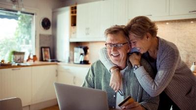 Kobieta przytulająca męzczyznę pracującego na laptopie w kuchnii.