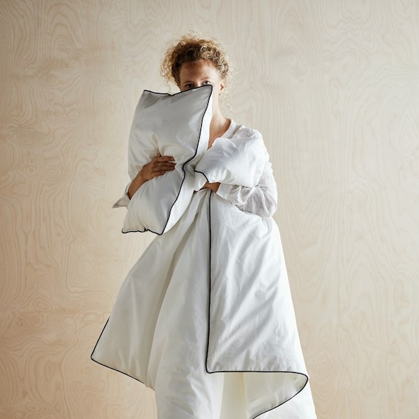 Kobieta przytulająca się do kołdry i poduszki na tle sklejki.