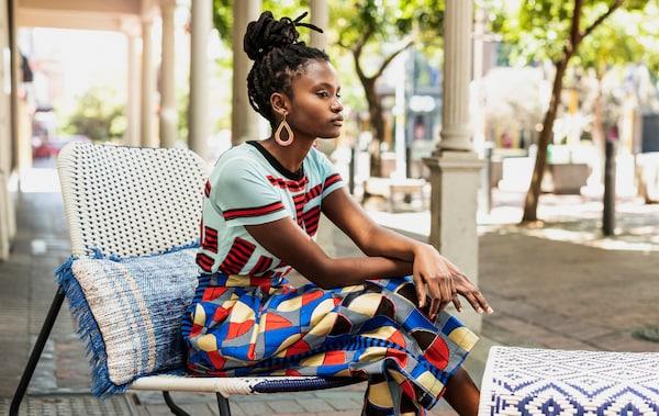 Kobieta w kolorowym ubraniu siedzi na krześle bujanym na świeżym powietrzu.