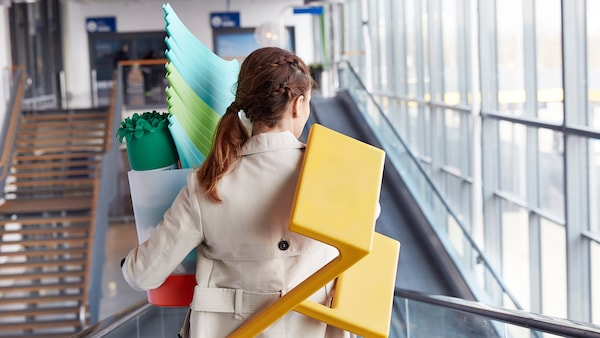Kobieta wychodząca ze sklepu IKEA ze stołkiem na ramieniu i zakupami w rękach.
