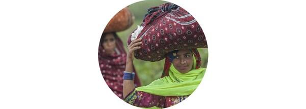 Kobiety niosące na głowach materiałowe torby ze świeżo zebraną bawełną ze zrównoważonych upraw.