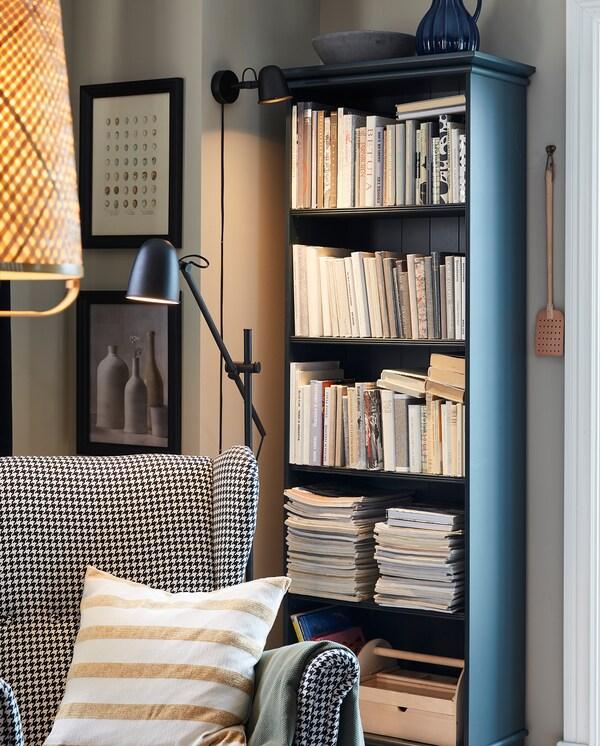Kodikkaassa lukunurkkauksessa SKURUP-lattiavalaisin, lepotuoli sekä tumman sinivihreä kirjahylly täynnä kirjoja.