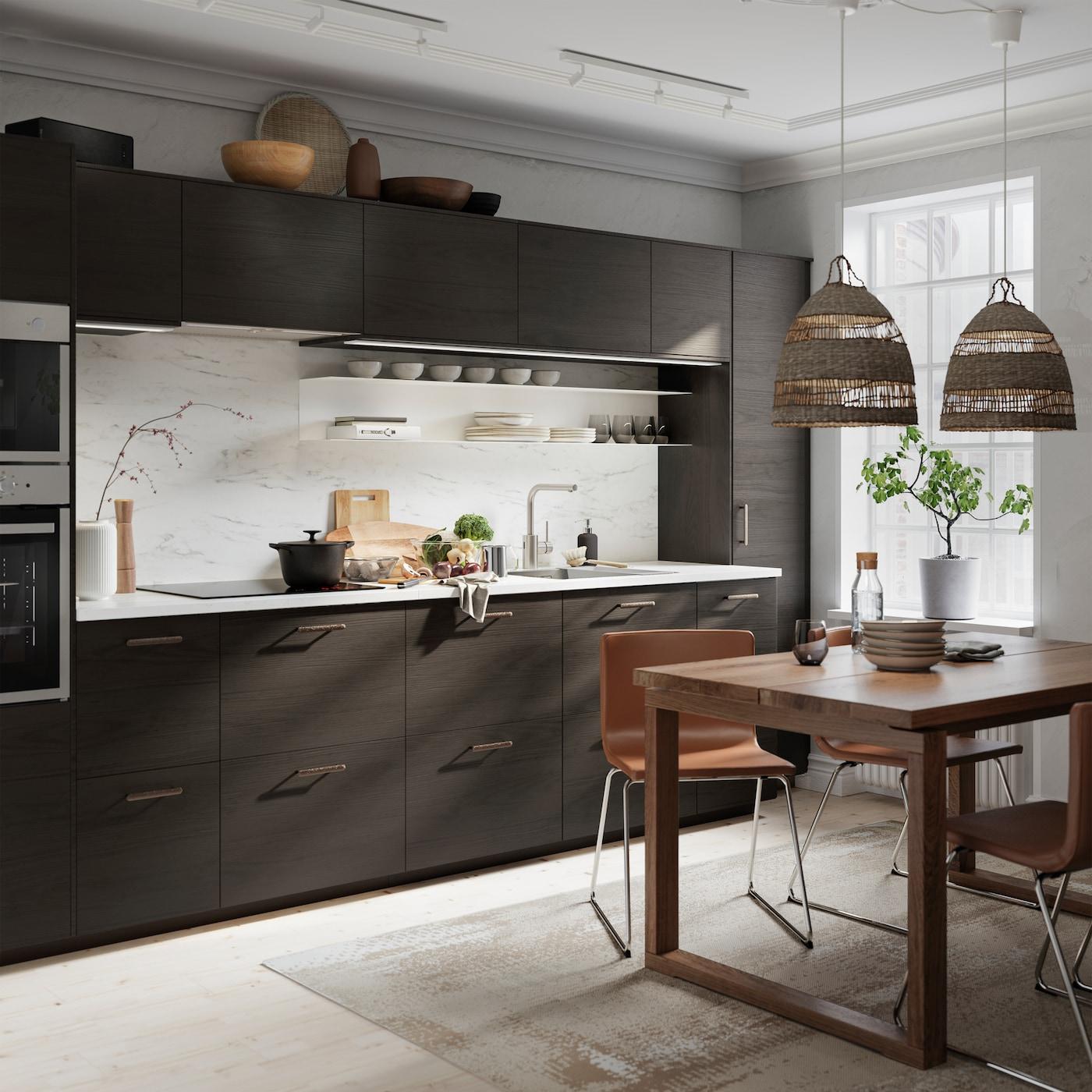 Kök med fronter i mörkbrunt askmönster och vit marmormönstrad väggplatta, träbord och läderstolar.