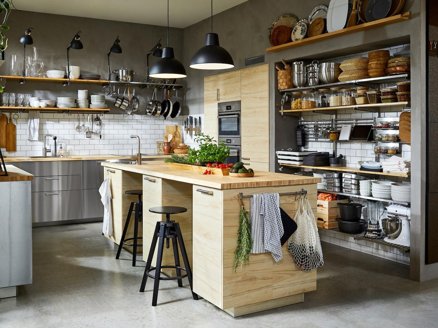 Kök med fronter i rostfritt stål, två svarta taklampor och rymlig köksö med två svarta barpallar.