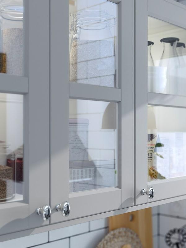 Köksskåp med tre vitrinluckor i härdat glas och ljusgrå träramar med fasade kanter.