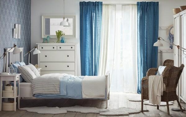 Közepes méretű hálószoba, fehér kétszemélyes ággyal, világoskék és szürke ágyneművel. Fehér fiókos szekrény, tükör és két éjjeliszekrény.