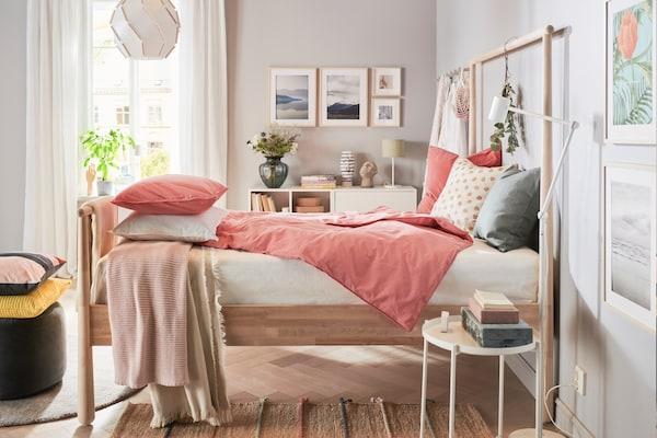 Koivusta tehty sänky, joka on pedattu vaaleanpunaisin lakanoin keskellä valoisaa makuuhuonetta.