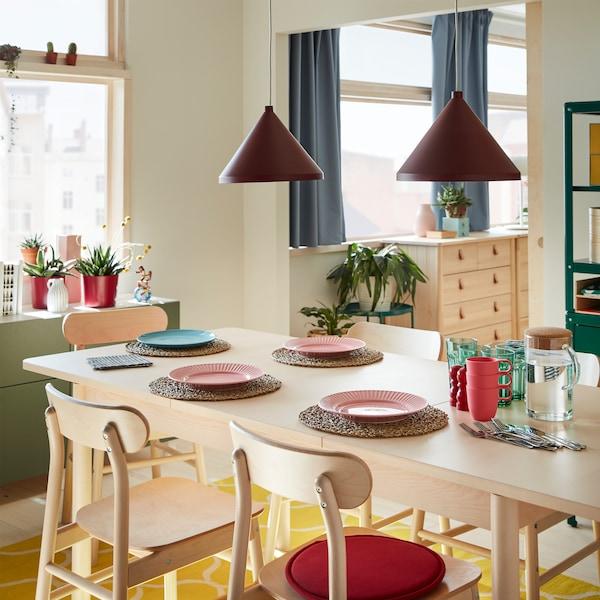 Koivusta valmistetut pöytä ja tuolit, keltainen matto, vaaleanpunaisia ja sinisiä lautasia, vihreitä laseja, aterimia ja kaksi tummanpunaista kattolamppua.