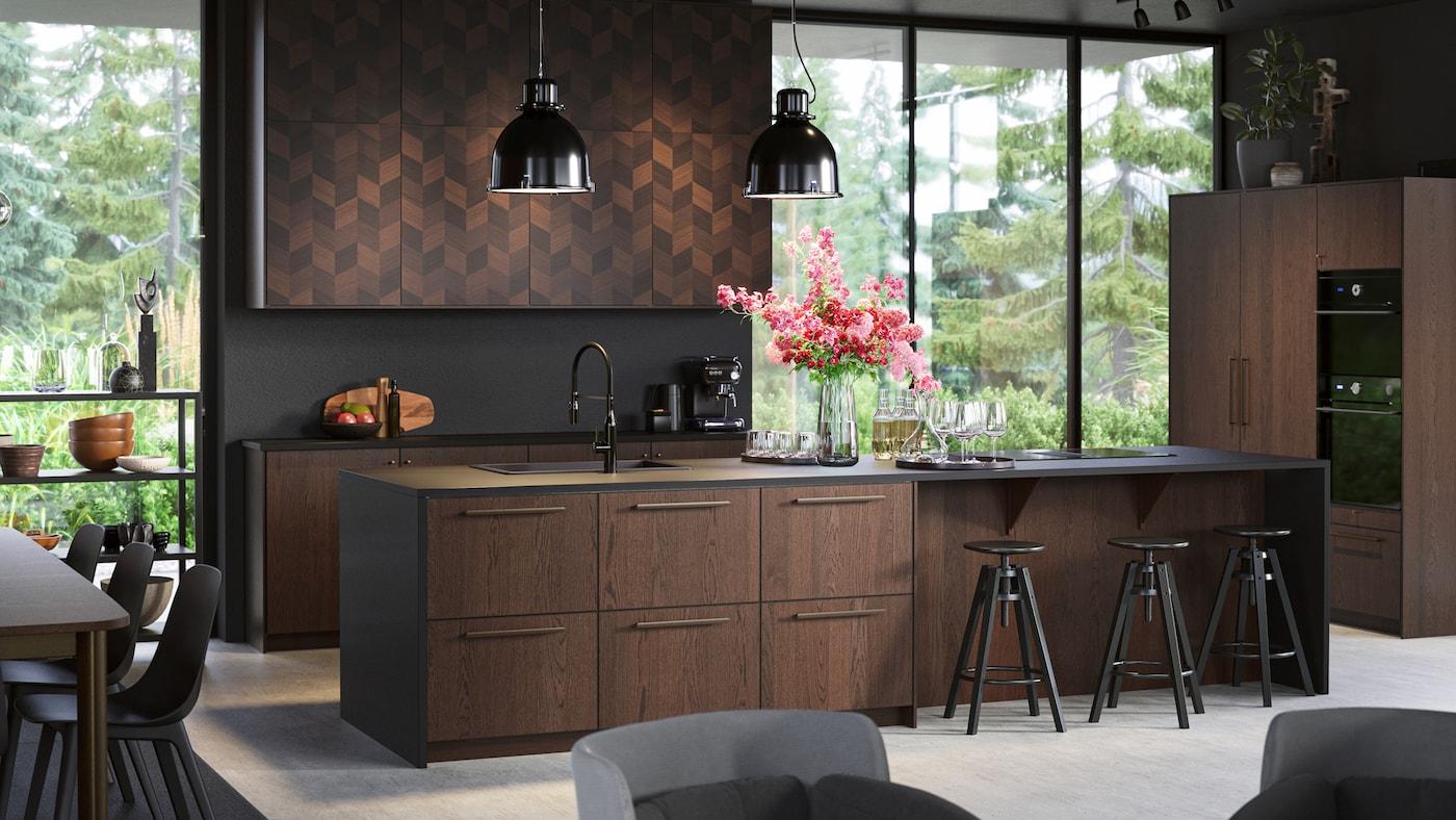 Køkken med åben indretning med vinduer fra gulv til loft, SINARP skuffer og HASSLARP låger, sorte loftlamper og bartaburetter.