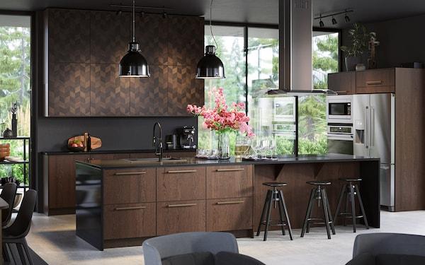 Køkken med SINARP skuffer og HASSLARP låger i mørkt træ, sorte loftlamper og bartaburetter.