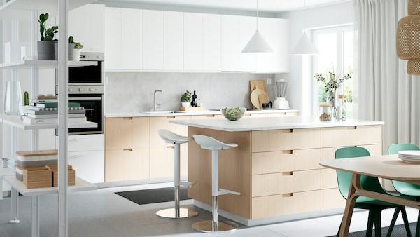 Køkken med skuffefronter og låger i hvid/bambus, en køkkenø, to barstole, to loftlamper og grønne stole.