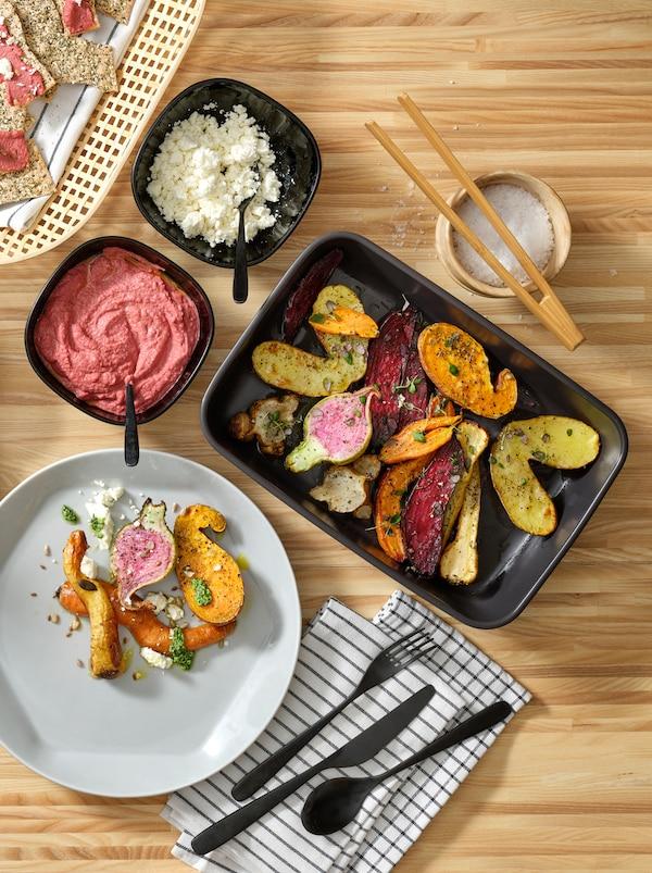Køkkenbord med en grå FORMIDABEL tallerken, der både er rund og sekskantet, og farvestrålende mad i sorte serveringsfade.