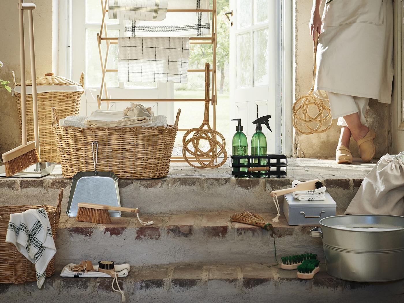 Kolekce výrobků BORSTAD vystavená přede dveřmi, vedle dveří stojí žena s plácačkou na koberce.