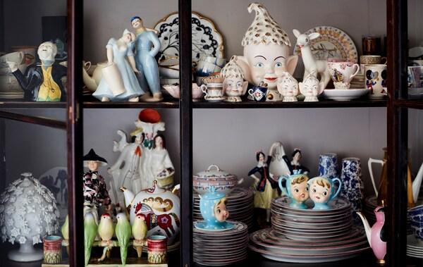 Koleksi hiasan china di dalam kabinet berpintu kaca.
