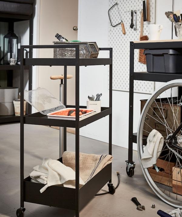 Kolica puna alata na praznom dijelu poda pokraj bicikla na kojem se trenutno provode manji popravci.