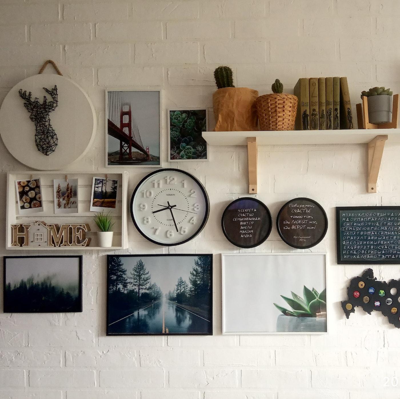 Коллаж на светлой стене из картин и часов