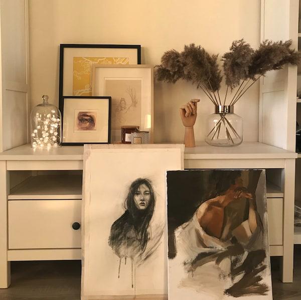 Коллаж в гостиной из картин и украшений на комоде