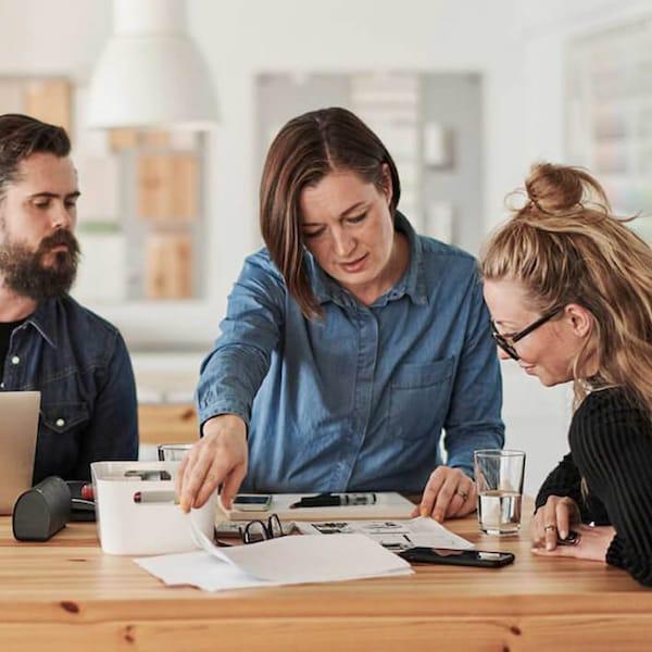 Kolme aikuista seisoo pöydän ympärillä suunnittelemassa.