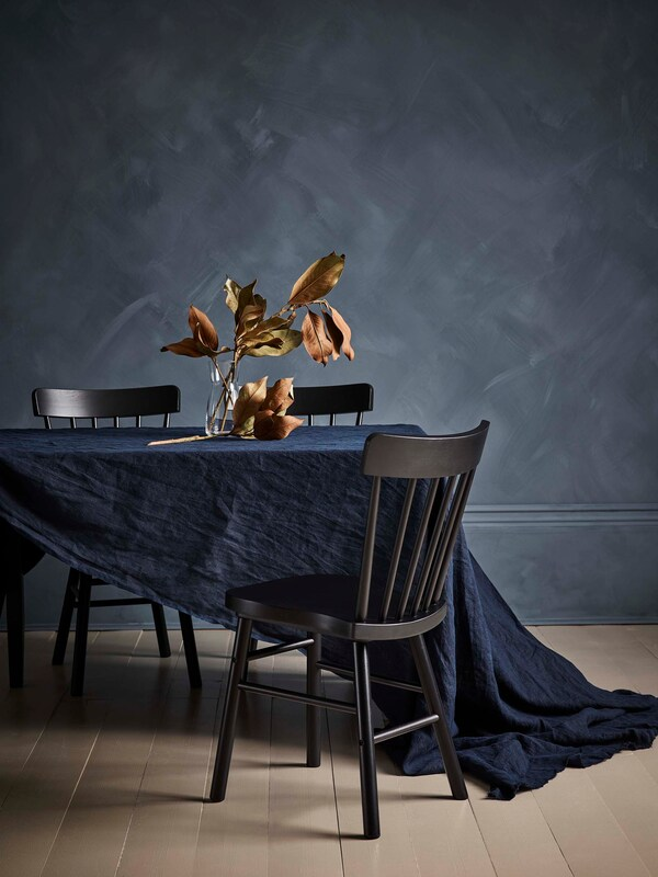 Kolme mustaa NORRARYD-tuolia sekä ruokapöytä, jonka päällä tummansininen pöytäliina.