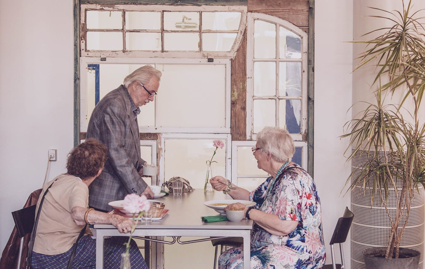 Kolme vanhempaa ihmistä istuu pöydän ääressä syömässä.