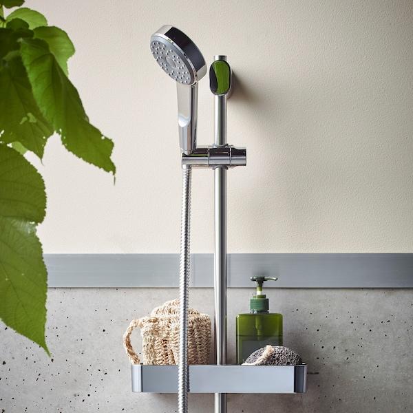 Kolore kromatuko BROGRUND dutxa-barra termostato-nahasgailuarekin; horman muntatuta dago eta belaki bat eta xaboi-dosifikagailu bat daude dutxako apal batean.