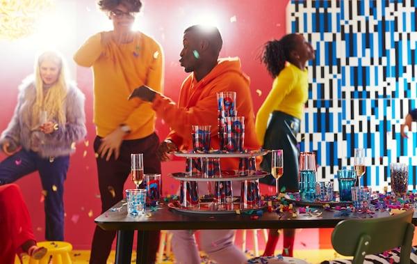 Kolorowa impreza z różnymi rodzajami szklanek, jak te z serii FRAMKALLA o zakrzywionych, odważnych wzorach w kolorze czerwonym i niebieskim.