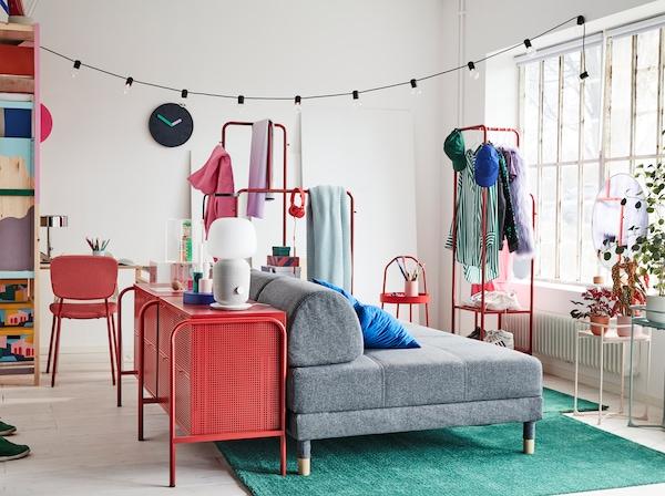 Kolorowa kawalerka z szarą rozkładaną sofą, dwoma zielonymi dywanami i czerwoną komodą.
