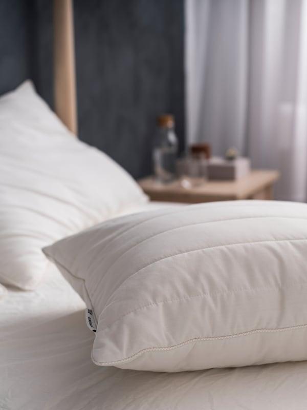 Komadi za krevet, poput RUMSMALVA ergonomskog jastuka bez jastučnice, na krevetu koji čeka svežu posteljinu.
