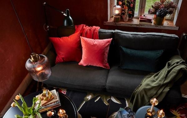 Kombinácia závesnej, stojacej a stolových lámp v obývacej izbe s pohovkou s farebnými vankúšmi, ktoré vytvárajú hrejivú a útulnú atmosféru.