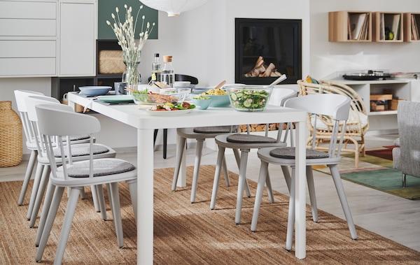 Kombinacija dnevne sobe i blagovaonice s kaminom, zidnim rješenjem za odlaganje i TINGBY blagovaonskim stolom s OMTÄNKSAM stolicama.
