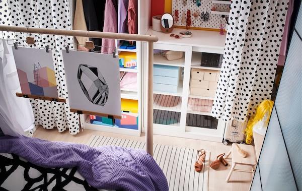 Комбинация из открытых и закрытых стеллажей вдоль стены; гардины отделяют проход. Также на фотографии виден край кровати.