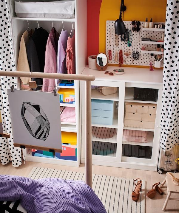 Kombination aus offener und geschlossener Aufbewahrung an einer Wand, u. a. mit dem SYVDE Schrank mit Vitrinentüren hinter dem Fussende eines Bettes.