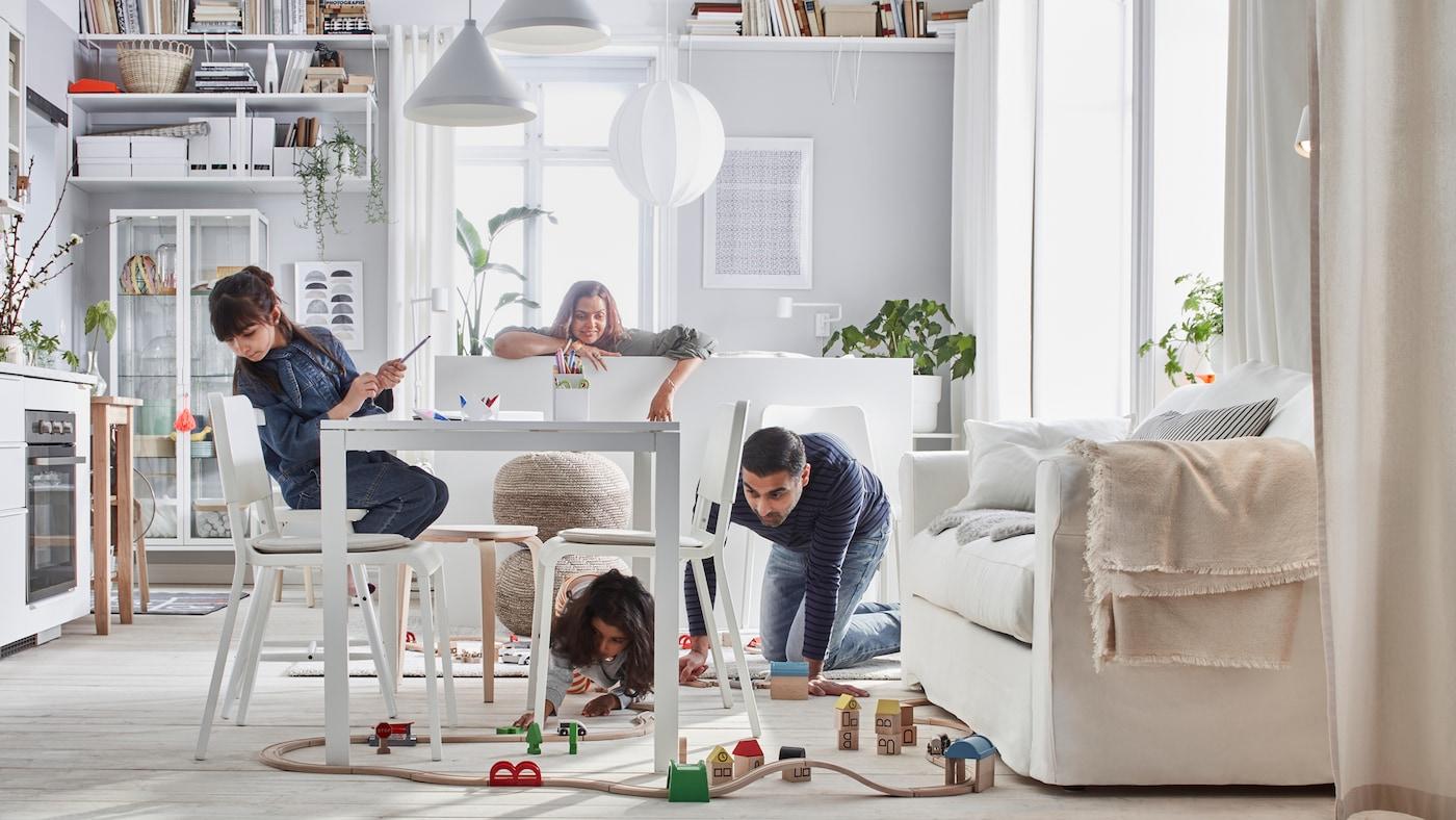 Kompaktný domov, kde sa rodina hrá so súpravou vláčikov LILLABO v miestnosti s posteľou, pohovkou, stolom, malou kuchyňou a úložnými priestormi.