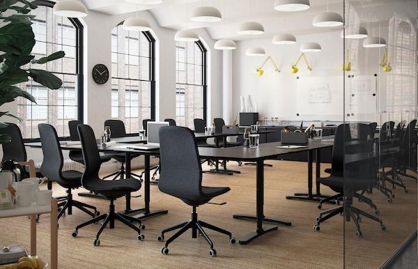 Konferenzraum mit vielen LÅNGFJÄLL Drehstühlen, schwarzen Tischen & gelben TERTIAL Lampen