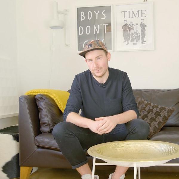Konrad sitzt auf einem braunen Ledersofa in seiner Wohnung.
