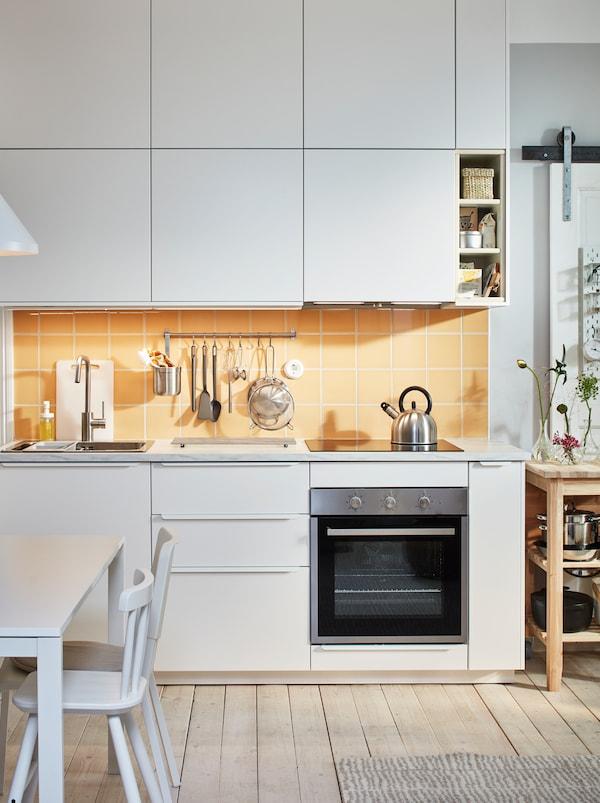 Konyhai munkalap mosogatóval, főzőlappal és konyhai eszközökkel, melyeket a fehér VEDDINGE előlappal felszerelt szekrények között tartanak.
