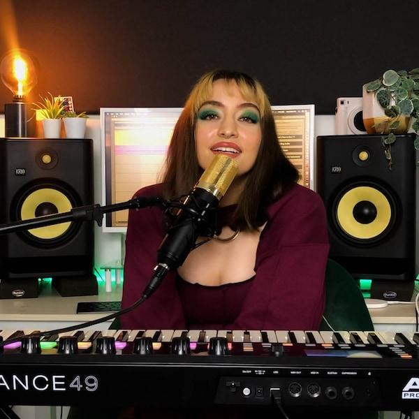 Kordelya sitht in ihrem Heimstudio vor einem Keyboard und Mikrophon