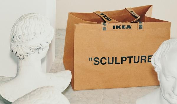 Коричневая сумка ИКЕА с принтом со словом «SCULPTURE» («скульптура»), лежащая между двумя белыми скульптурами.