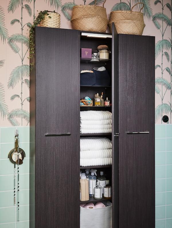 Korkea mustanruskea kaappi tarjoaa säilytystilat kylpyhuoneen tavaroille ja pyyhkeille. Taustalla lehtikuvioinen tapetti.