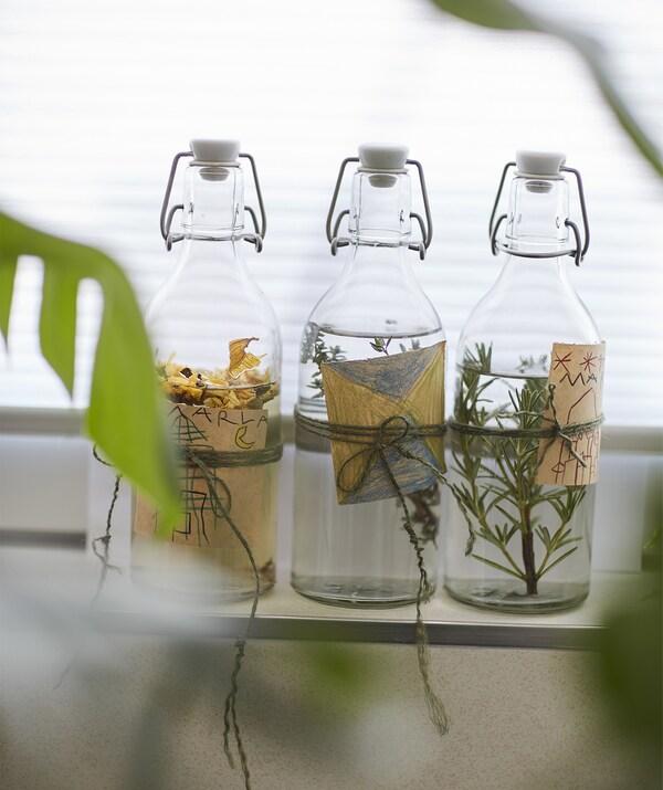 KORKEN Flaschen mit Verschluss mit selbst gemachten Etiketten, darin Badeessenzen