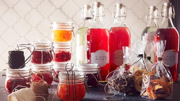 Korken zárható üvegek és befőttesüvegek szörüökkel és gyümölcsökkel megtöltve.