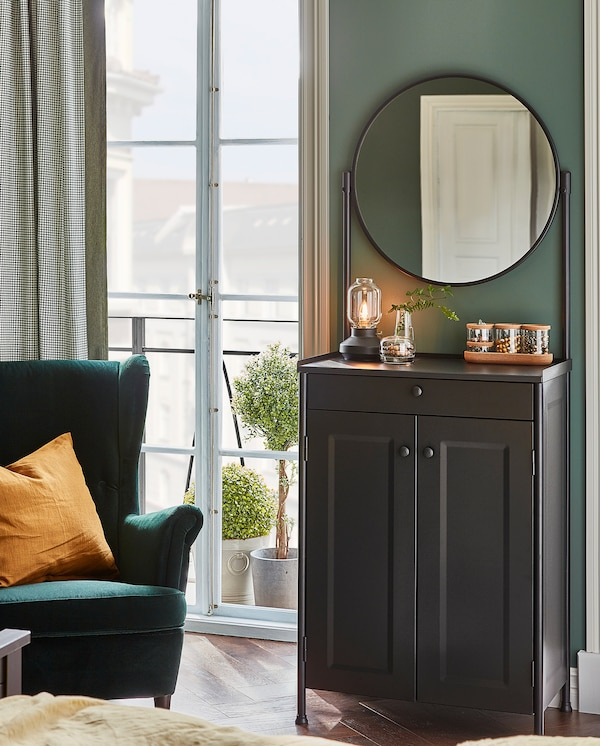 KORNSJÖ element s ogledalom pokraj zida. Stolna lampa, vaza i staklenke s poklopcima stoje na njegovoj površini.