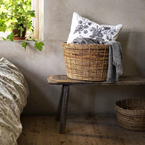 Корзина ТИЛЛЕВИПС из волокон банановых листьев, в которой лежат одеяла и белая подушка с цветочным узором, стоит на скамье.