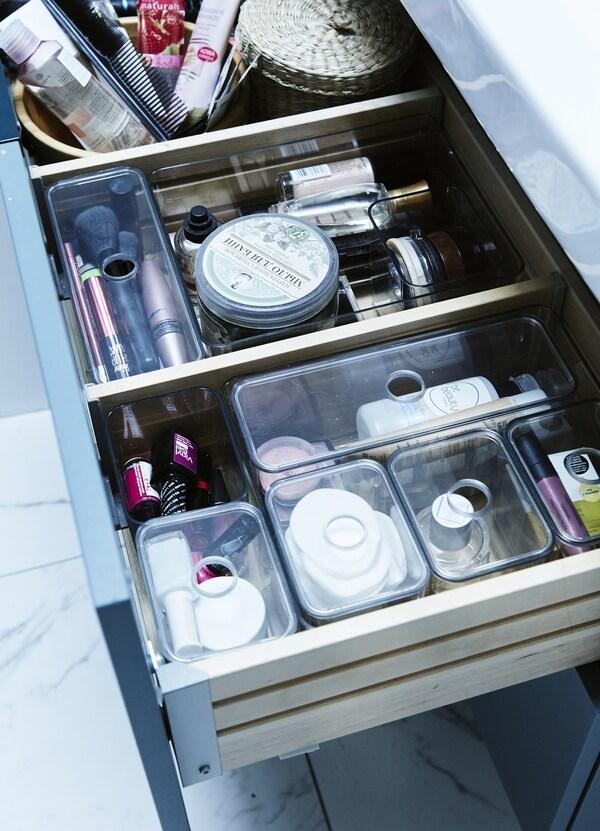 Kosmetik dan kelengkapan dandanan diri tersusun di dalam kotak dan sisipan dulang di dalam laci bilik mandi.