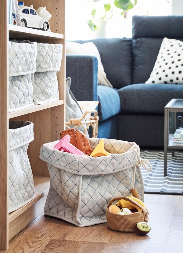 Kosze z miękkiej tkaniny IKEA SKUBBARE z dziecięcymi zabawkami u podstawy regału.