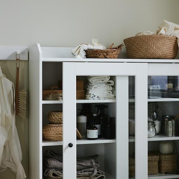 Koszule na wieszakach, witryna z pudełkami i koszem z naturalnych materiałów, poskładane tekstylia i produkty do prania.