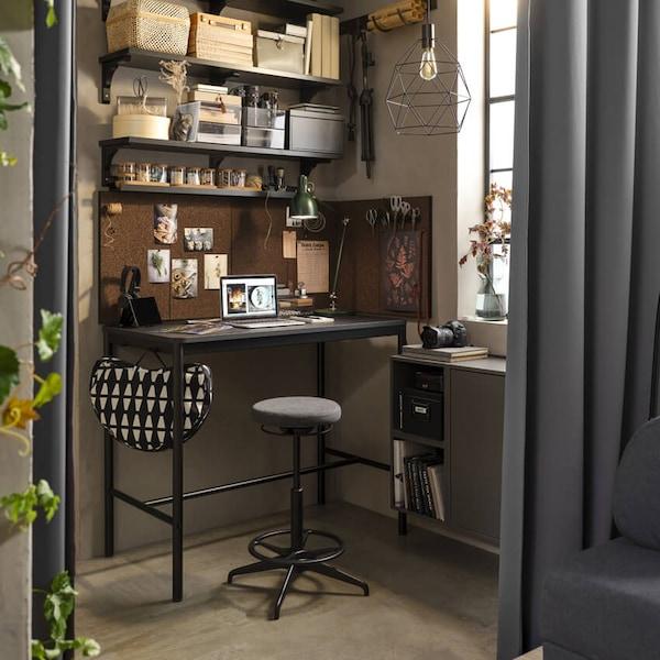 Kotitoimisto, jossa ikkunan edessä TOMMARYD-työpöytä, jonka edessä aktiivityötuoli. Pöydän reunassa roikkuu BYLLAN-sylitaso.